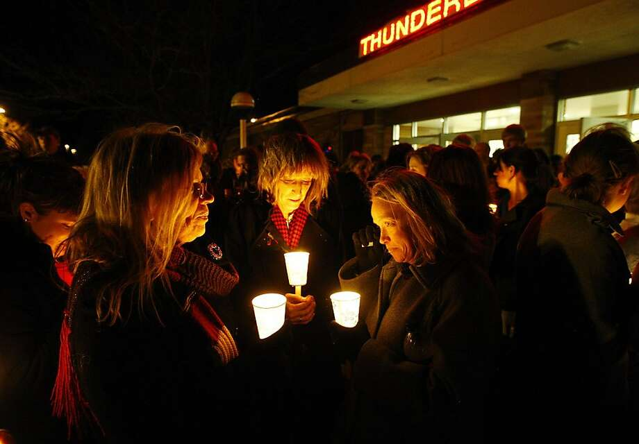Mourners stand outside of Swede Erickson Thunderbird Gym during a candlelight vigil after a memorial service for Casper College instructors Jim Krumm and Heidi Arnold on Tuesday, Dec. 4, 2012, in Casper, Wyo. Photo: Dan Cepeda, Associated Press