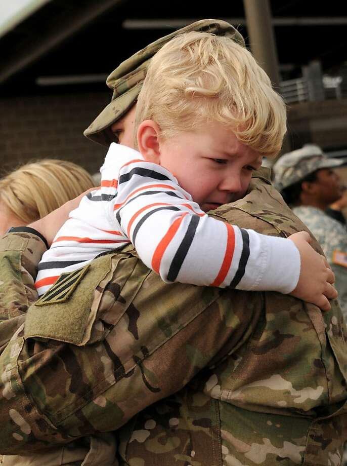 Three-year-old Cain Mullins is emotional as he hugs his father, Army Sgt. Christopher Mullins, Tuesday morning Dec. 4, 2012 at Fort Stewart, Ga. The sergeant and about 200 other soldiers with the 1st Battalion, 64th Armor Regiment of the 3rd Infantry Division's 2nd Brigade Combat Team returned home Tuesday after nine months in Afghanistan. Photo: Corey Dickstein, Associated Press