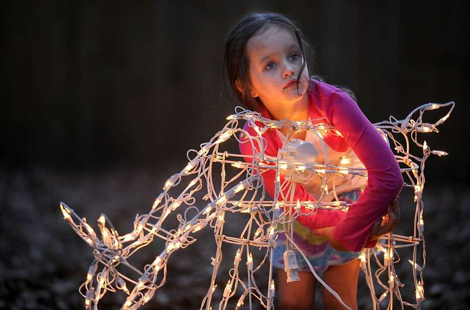 Aubrey Harper hugs a reindeer decoration as her father  puts up Christmas lights in their house's front yard in Tanner, Ala. Tuesday, Dec. 4, 2012. Photo: Jeronimo Nisa, Associated Press