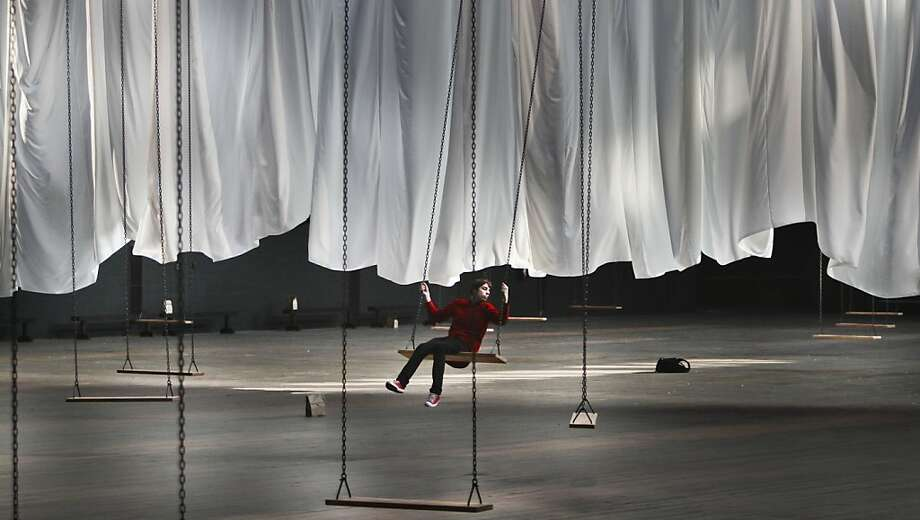 "Max Fauconnier swings alone during a preview of Ann Hamilton's multimedia art installation ""the event of a thread,"" on Tuesday, Dec. 4, 2012 at the Park Avenue Armory in New York.  The participatory installation featuring 42 swings suspended from the Armory's elliptical ceiling and tethered to a massive white cloth, is Hamilton's first large scale project in the city in more than ten years and opens Dec. 5 for a month. Photo: Bebeto Matthews, Associated Press"