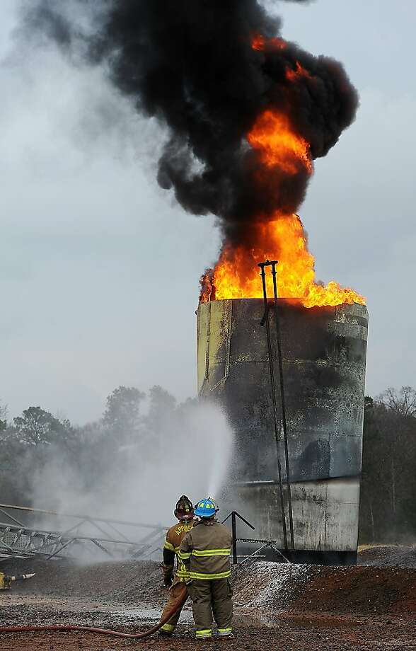 Firefighters from three volunteer departments use water to cool down a fire in a salt water storage tank at a natural gas well near Nacogdoches, Texas, on Tuesday, Dec. 4, 2012. Katie McCullin, manager media relations and corporate development for Chesapeake Energy Corp. in Shreveport, La., said late Tuesday the fire at the company well site was triggered by a lightning strike. There were no injuries and natural gas production at the well was shut down pending repairs to above ground equipment. Photo: Andrew D. Brosig, Associated Press