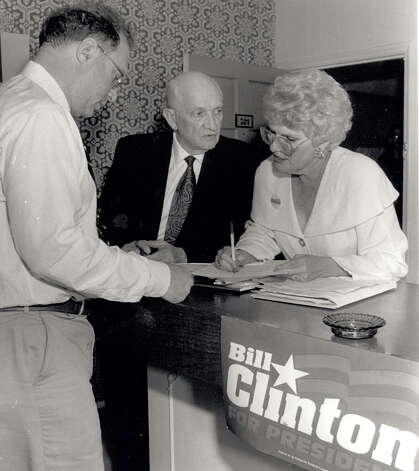 Sam Rhine gives results from Precinct 65 to Jack Brooks and Sue Ball at the Clinton Steering Committee Party at the Quality Inn in 1992. Enterprise file photo
