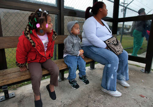 Denver Chretien, 3, and Donovan Chretien, 2, wait with their mom Malena, right, at the bus stop on Scott Street Wednesday, Dec. 5, 2012, in Houston. Malena said the weather is cold this morning. Photo: Cody Duty, Houston Chronicle / © 2012 Houston Chronicle