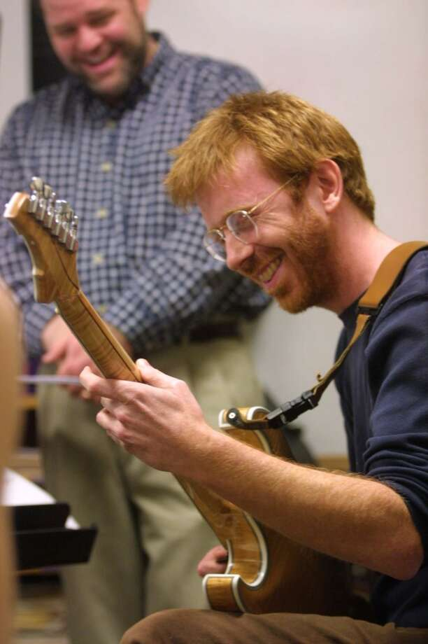 Trey Anastasio, lead vocalist, guitarist, and composer with the band Phish, gets into the music as conductor Troy Peters listens during rehearsal with the Vermont Youth Orchestra, Sunday, Jan. 28, 2001, at Burlington high School in Burlington, Vt. Anastasio is playing in concert with the orchestra this weekend. (AP Photo/Alden Pellett) (AP)