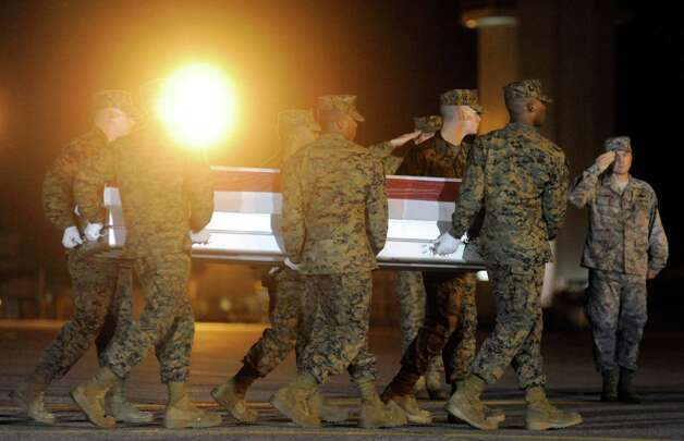 A Marine carry team moves a transfer case containing the remains of Lance Cpl. Anthony J. Denier Tuesday, Dec. 4, 2012 at Dover Air Force Base, Del. According to the Department of Defense, Denier, 26, of Mechanicville, N.Y., died Dec. 2, 2012 while conducting combat operations in Helmand province, Afghanistan. (AP Photo/Steve Ruark) Photo: Steve Ruark
