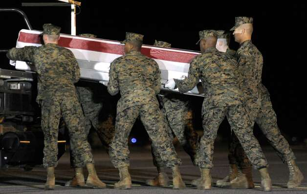 A Marine carry team lifts a transfer case containing the remains of Lance Cpl. Anthony J. Denier Tuesday, Dec. 4, 2012 at Dover Air Force Base, Del. According to the Department of Defense, Denier, 26, of Mechanicville, N.Y., died Dec. 2, 2012 while conducting combat operations in Helmand province, Afghanistan. (AP Photo/Steve Ruark) Photo: Steve Ruark