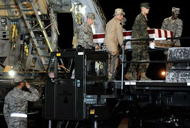 A carry team moves a transfer case containing the remains of Marine Lance Cpl. Anthony J. Denier Tuesday, Dec. 4, 2012 at Dover Air Force Base, Del. According to the Department of Defense, Denier, 26, of Mechanicville, N.Y., died Dec. 2, 2012 while conducting combat operations in Helmand province, Afghanistan. (AP Photo/Steve Ruark) Photo: Steve Ruark