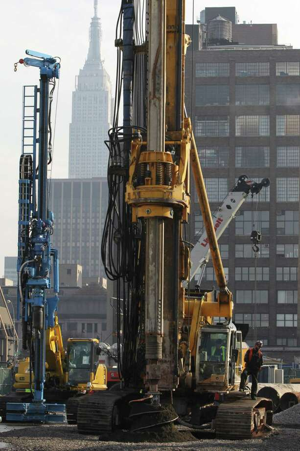 The Empire State building is seen in the background as a BG 40 drill rig breaks ground for a new neighborhood called Hudson Yards, Tuesday, Dec. 4, 2012 in New York.  The ambitious development is meant to transform the largest undeveloped property in Manhattan from an isolated rail yard into a sleek new neighborhood of spiky high-rises and graceful parks. Photo: Mary Altaffer, AP / AP
