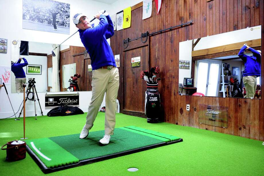 PGA Golf Professional Tyler Lower hits balls at his indoor golf facility, Greenlight Golf, in Norwalk.  Lower renovated a barn on his property to accomadate lessons for golfers of all skill levels. Photo: Autumn Driscoll / Connecticut Post