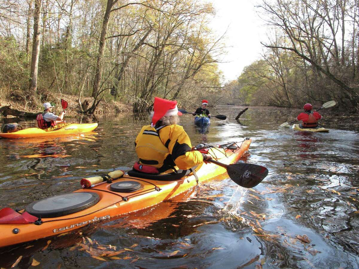 Kayakers and canoers paddle home after gathering mistletoe along the Upper Little River near Lillington, N.C., on Saturday, Dec. 1, 2012. They were part of the 30th annual Sprig Outing, which started as a fundraiser for local conservationists. AP Photo/Allen Breed)