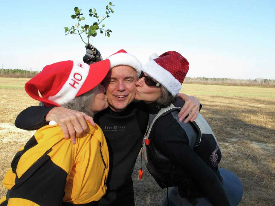 Nate Jackson of Chapel Hill, N.C., gets a smooch under the mistletoe from Camille Warren, left, and his neighbor Joan Monnig along the bank of the Upper Little River near Lillington, N.C., on Saturday, Dec. 1, 2012. They were part of the 30th annual Sprig Outing. Photo: Allen Breed, AP / AP