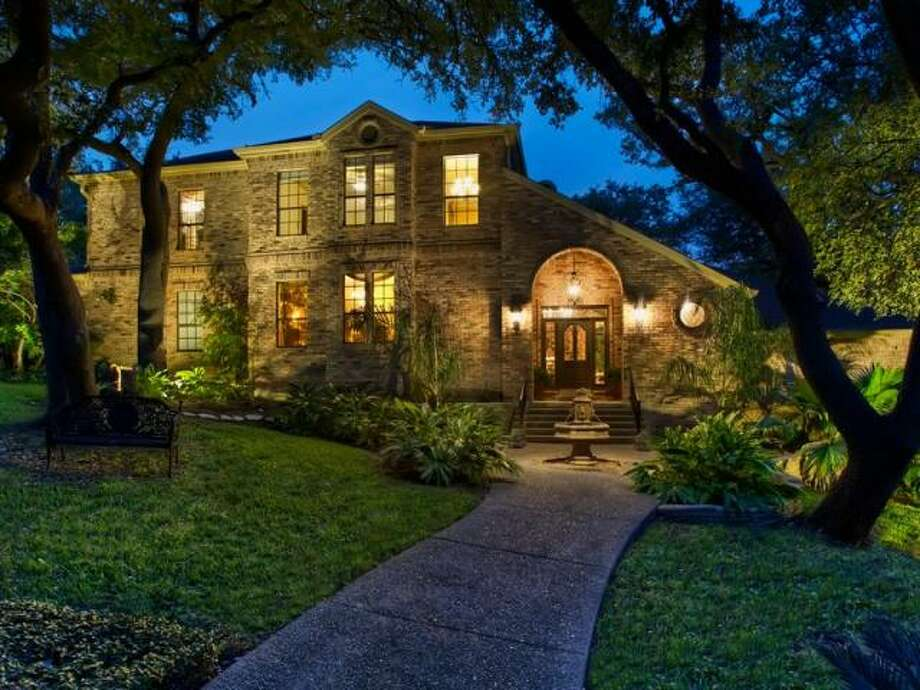 Especially at night, the brick facade to 302 Bluff Crest glows. Complementing the aesthetic is a fountain and tropical plantings before the front entrance. (Kuper Sotheby\\\'s International Realty)