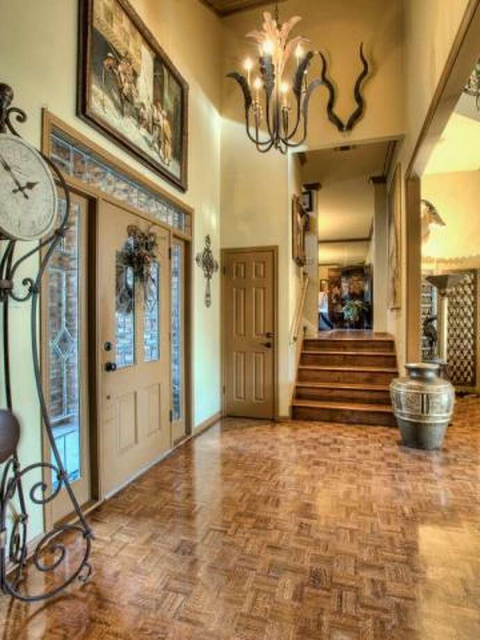 Upon entering the home, one is greeted by a foyer with a high ceiling and hanging fixture. The front door is framed by windows that draw natural light indoors. (Kuper Sotheby\\\'s International Realty)