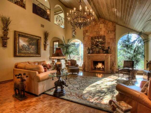 The fireplace in the living room scales to the high ceiling and two large, arched windows on either side bring light into the room. (Kuper Sotheby\\\'s International Realty)
