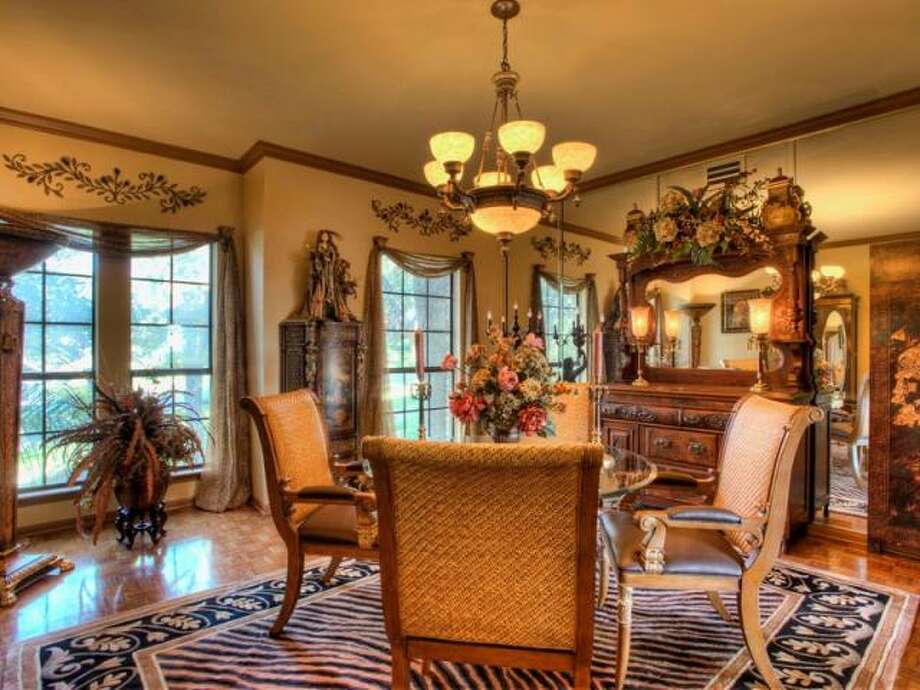 The formal dining room continues the theme of ample windows and custom hanging light fixtures. (Kuper Sotheby\\\'s International Realty)