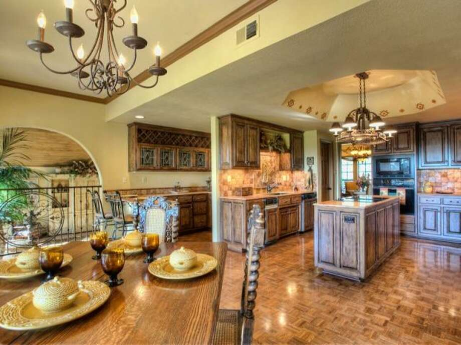 With a breakfast bar, eating area and center island, the kitchen offers multiple places to dine. Behind the breakfast bar is a separate preparation area with glass front cabinets and a wet bar. (Kuper Sotheby\\\'s International Realty)