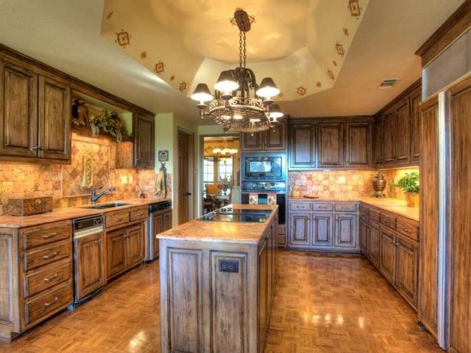 The kitchen appliances are fronted with the same wood facade as the cabinets to neatly blend in with the rustic-stained cabinetry. (Kuper Sotheby\\\'s International Realty)