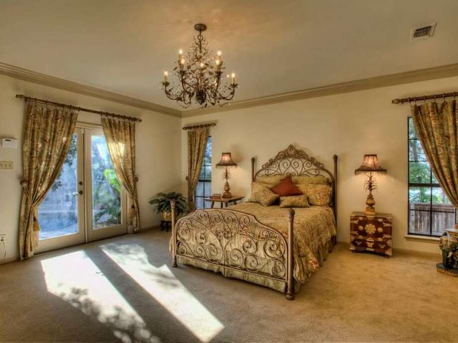 The master bedroom has a custom chandelier of its own, along with soft carpeting and French doors which lead to the back. (Kuper Sotheby\\\'s International Realty)