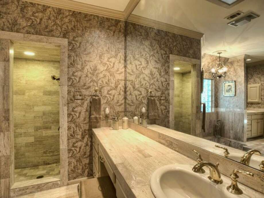 The master bathroom has a large mirror, ample vanity space and a stone shower stall. (Kuper Sotheby\\\'s International Realty)