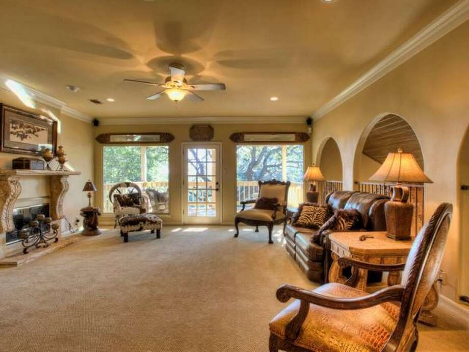 The family room boasts a fireplace as well. One can also walk out to the second floor balcony that overlooks the backyard and the salt water pool. (Kuper Sotheby\\\'s International Realty)