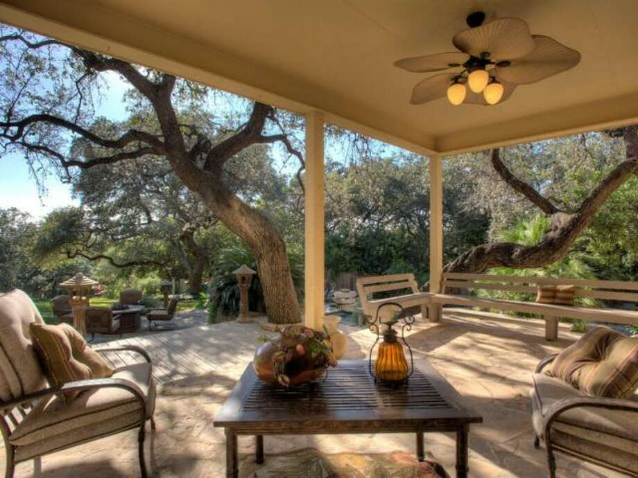 Below the balcony is a covered patio, also with a ceiling fan, bench seating and a view of the yards many trees and excellent landscaping. (Kuper Sotheby\\\'s International Realty)