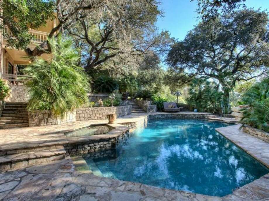 The salt water pool and hot tub are set in a stone patio and surrounded tropical plants and mature trees. (Kuper Sotheby\\\'s International Realty)