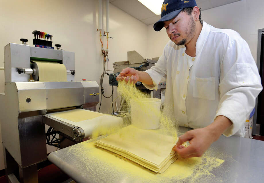 Carlos Ariza sprinkles corn flower over pasta squares that he is making at Villarina's Pasta and Fine Foods in Danbury, Wednesday, Dec. 5, 2012.  The squares are used to make different types of pasta. Photo: Carol Kaliff / The News-Times