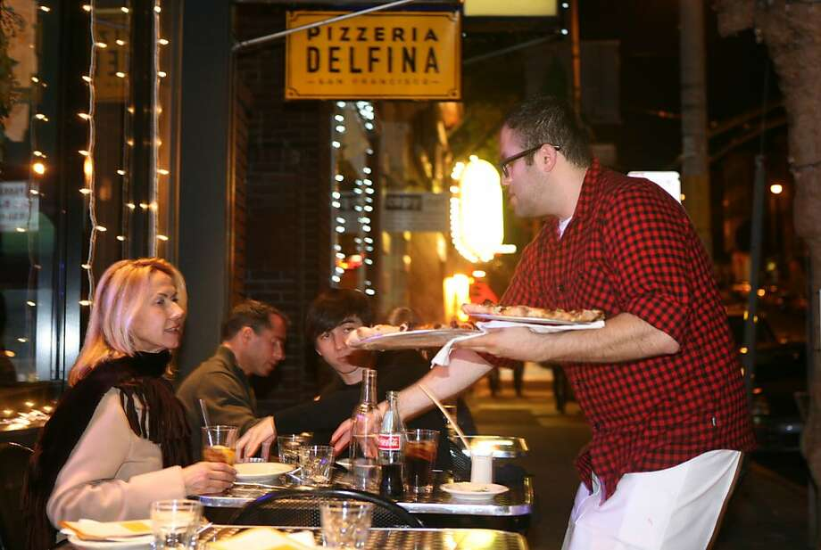 Diners have a meal outside at Pizzeria Delfina, which has two locations in S.F. and will remodel a downtown Burlingame furniture store for a third location. Photo: Lea Suzuki, The Chronicle
