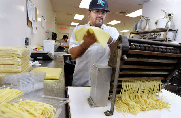 Lazaro Illescas cuts and packages pasta at Villarina's Pasta and Fine Foods in Danbury, Wednesday, Dec. 5, 2012. Photo: Carol Kaliff / The News-Times