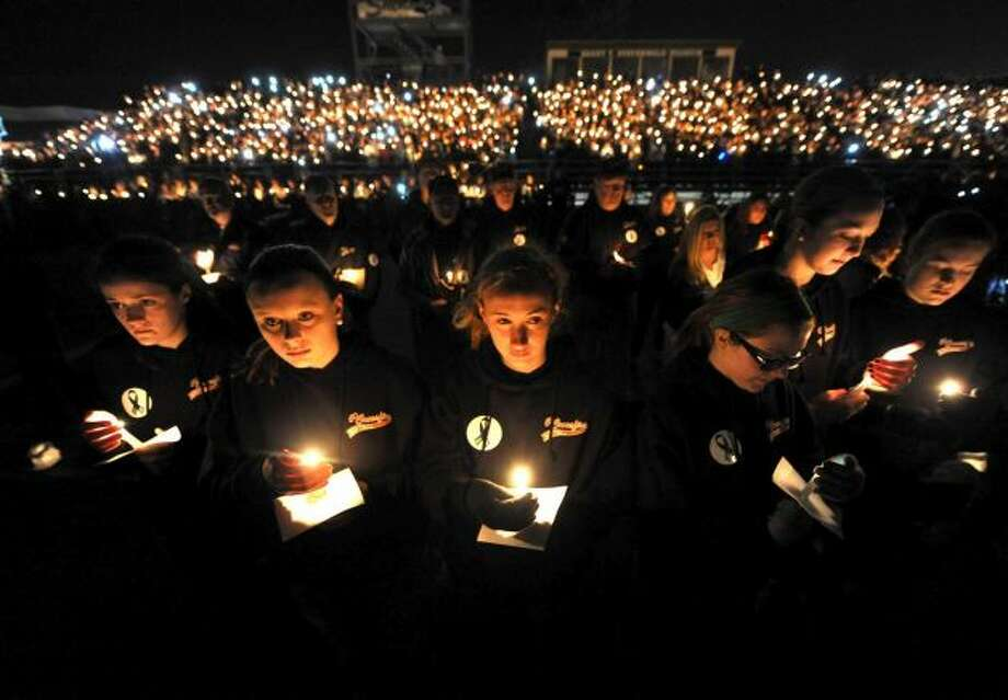 Member of the Capital District Crossfire girls softball team and teammates of Deanna Rivers join thousands during a candlelight vigil and memorial service for the Shen crash victims at Shenendehowa High School in Clifton Park, NY Tuesday Dec. 4, 2012. Shen students Chris Stewart and Deanna Rivers died in the crash with Matt Hardy and Bailey Wind being seriously injured.(Michael P. Farrell/Times Union)