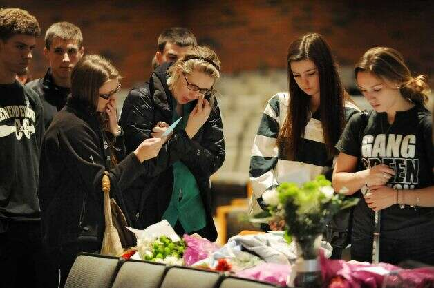 Students get emotional at a memorial set up in the auditorium at Shenendehowa High School Monday Dec. 3, 2012 in Clifton Park, N.Y. The memorial is set up for students to grieve together, to leave notes and flowers to honor the lives of Chris Stewart and Deanna Rivers, and to offer wishes for the emotional and physical recovery of Matt Hardy and Bailey Wind. Many students wrote the #69 for Chris and #19 for Deanna on their hands today. (Lori Van Buren / Times Union)