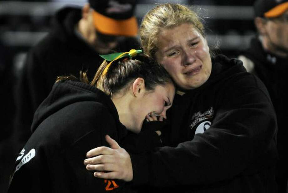 Members of the Capital District Crossfire girls softball team River Ward, left, and Hannah Sears teammates of Deanna Rivers join thousands during a candlelight vigil and memorial service for the Shen crash victims at Shenendehowa High School in Clifton Park, NY Tuesday Dec. 4, 2012. Shen students Chris Stewart and Deanna Rivers died in the crash with Matt Hardy and Bailey Wind being seriously injured.(Michael P. Farrell/Times Union)