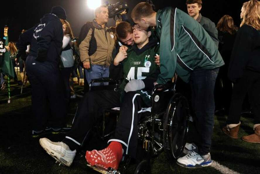 Crash survivor Matt Hardy, center, is greeted by football teammates after arriving by medical van du