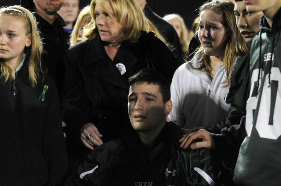 Member of the Capital District Crossfire girls softball team and teammates of Deanna Rivers join thousands during a candlelight vigil and memorial service for the Shen crash victims at Shenendehowa High School in Clifton Park, NY Tuesday Dec. 4, 2012. Shen students Chris Stewart and Deanna Rivers died in the crash with Matt Hardy and Bailey Wind being seriously injured. (Michael P. Farrell/Times Union)