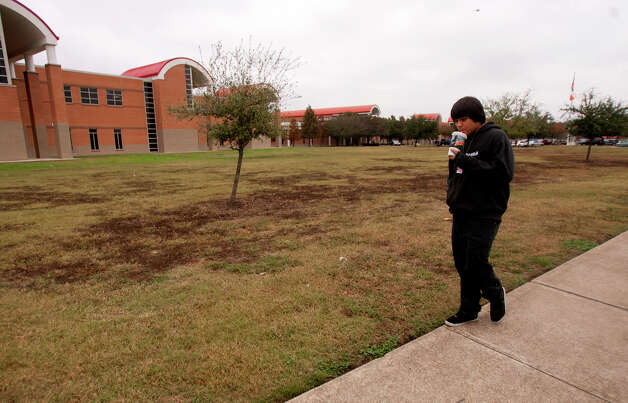 Juan Gallo walks in front of North Shore High School after a shooting occurred Wednesday, Dec. 5, 2012, in Houston. Police say a high school student shot himself after being taken into custody for having a gun at the school when he allegedly shot himself with another gun while in custody. Photo: Cody Duty, Houston Chronicle / © 2012 Houston Chronicle