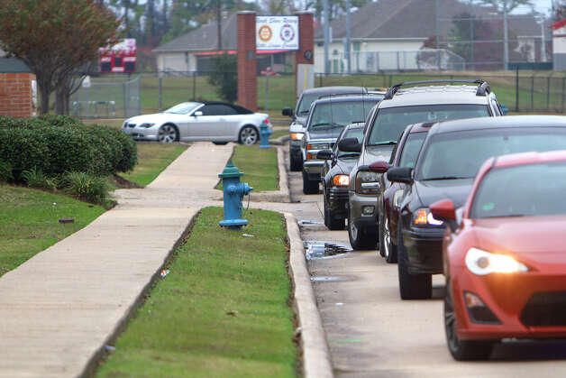 Cars line up to pick up students outside of North Shore High School after a shooting occurred Wednesday, Dec. 5, 2012, in Houston. Police say a high school student shot himself after being taken into custody for having a gun at the school when he allegedly shot himself with another gun while in custody. Photo: Cody Duty, Houston Chronicle / © 2012 Houston Chronicle