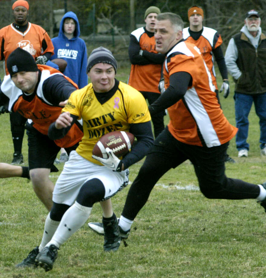 The elusive Brian Kerwin-Welsh of the A-1 Auto Body and JoJo's Deli Dirty Dozen proves a tough guy to tag for Sole defenders during New Milford Parks & Recreation's men's touch football championship game at Marx Field, Nov. 25, 2012 Photo: Norm Cummings