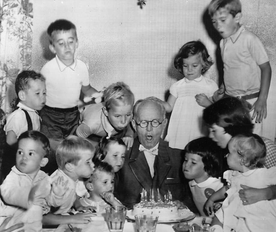 Grandchildren of Joseph P. Kennedy help him blow out the candles on a cake to celebrate his 72nd birthday. Photo: AP Wirephoto