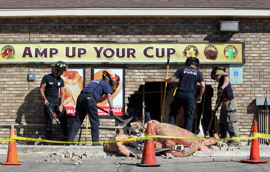 San Antonio firefighters clean up debris at a Valero Corner Store on the 12,300 block of Wetmore road after an SUV crashed into the side of the building about 11:30 a.m. Wednesday December 5, 2012. San Antonio Fire Captain Michael Wagner said the driver of the vehicle fled the scene and nobody in the store was injured. Photo: John Davenport / Express-News