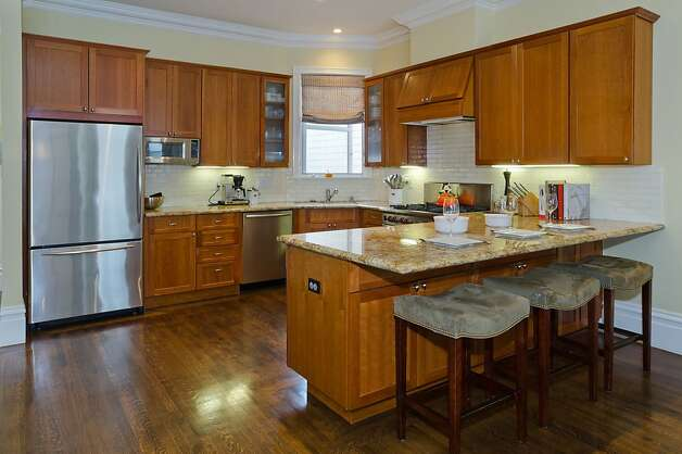 The breakfast bar and remodeled kitchen features stainless steel appliances and granite countertops. Photo: Reflex Imaging