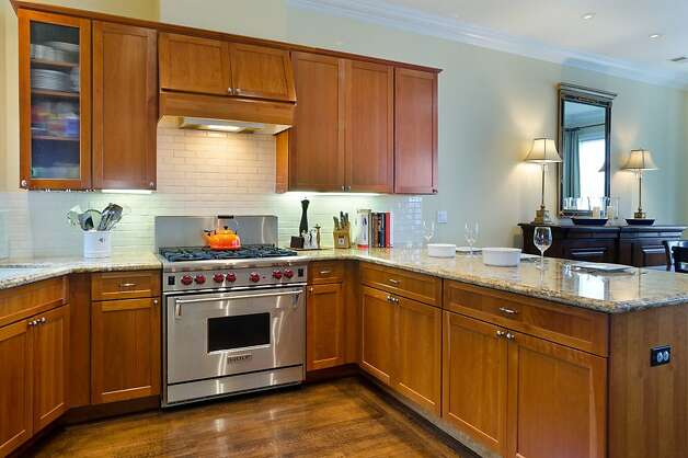 The six-burner Wolf professional range and granite countertops are features of the kitchen. Photo: Reflex Imaging