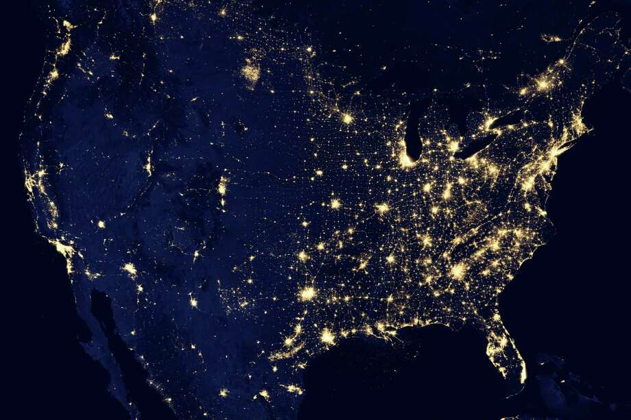 "In this image provided by NASA, the United States of America is seen at night from a composite assembled from data acquired by the Suomi NPP satellite in April and October 2012. The image was made possible by the new satellite's ""day-night band"" of the Visible Infrared Imaging Radiometer Suite (VIIRS), which detects light in a range of wavelengths from green to near-infrared and uses filtering techniques to observe dim signals such as city lights, gas flares, auroras, wildfires, and reflected moonlight. Photo: NASA"