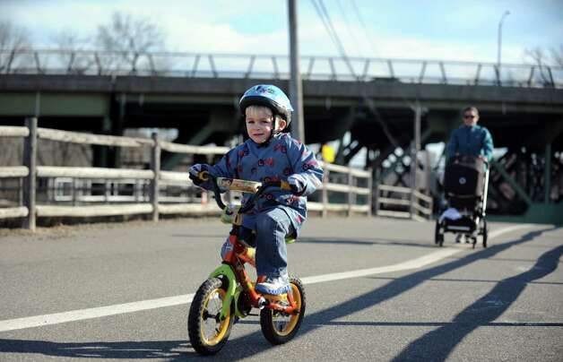 Three-year-old Jack Dunford pedals ahead of mom, Carly Dunford, of Shelton, and seven-month-old brother, Miles, Wednesday, Dec. 5, 2012 at the Derby Greenway. Photo: Autumn Driscoll / Connecticut Post