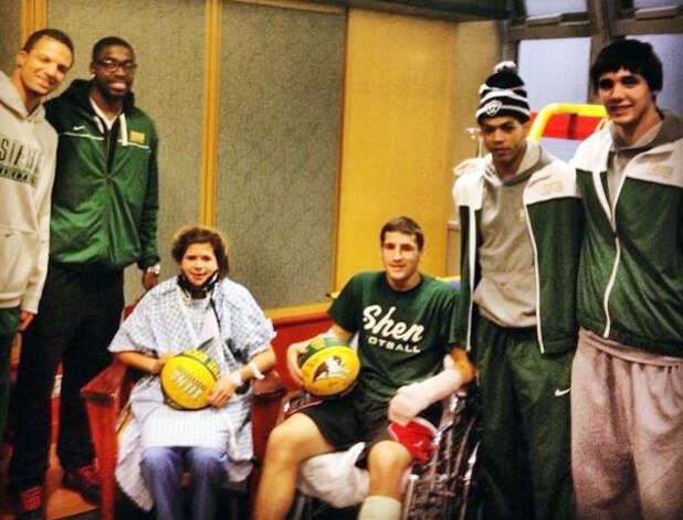 Bailey Wind, 17, and Matt Hardy, 17, seated, were visited by O.D. Anosike, second from left, and other members of the Siena men's basketball team on Wednesday. The players visited Wind and Hardy at Albany Medical Center Hospital where the teens were being treated for injuries they suffered in a Saturday night vehicle crash on the Northway. Anosike posted the photograph on Twitter. (O.D. Anosike via Twitter)