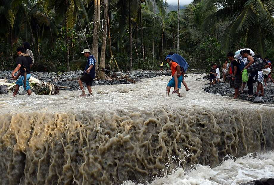 Death toll rises:Villagers cross a flooded road destroyed at the height of Typhoon Bopha in Andap, New Bataan town, in the Philippine province of Compostela Valley. The storm killed at least 274 people, and hundreds remain missing. Photo: Ted Aljibe, AFP/Getty Images