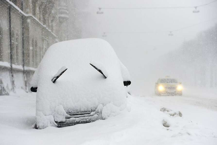 Saab story: A parked car grimaces during a snowstorm in Stockholm.