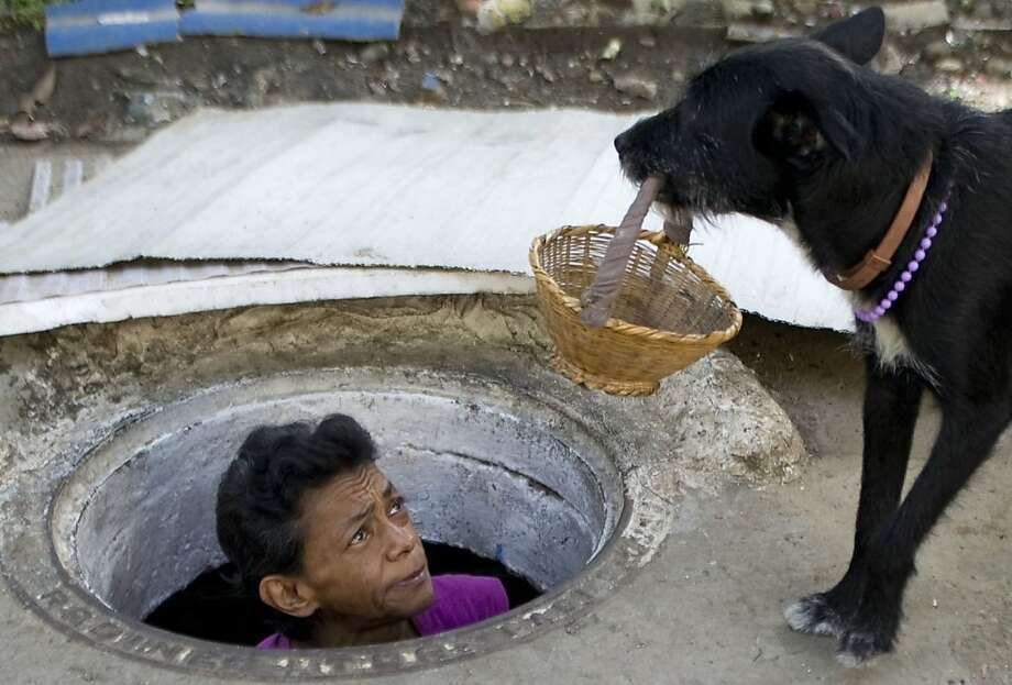 "Put the biscuit in the basket, please:Sixty-two-year-old Maria Garcia gives her dog a look at her ""home"" in Medellin, Colombia. She and her husband have resided in the city sewer for more than 20 years. Their living space is 10 feet long by 7 feet wide by 4.5 feet high. Photo: Raul Arboleda, AFP/Getty Images"
