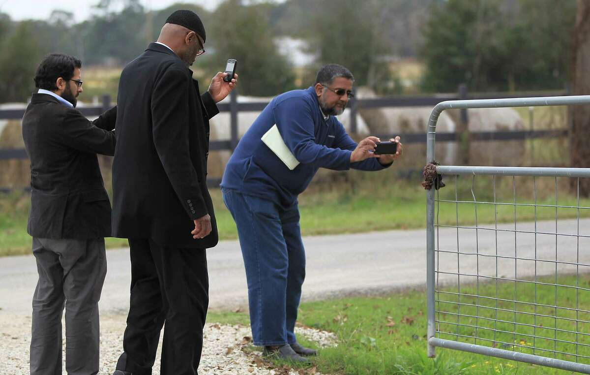 Fahad Tasleem, resident Imam of the Islamic Outreach Center in Cypress, with Mustafaa Carroll, center and Ilyas Choudry, board member of ICNA (Islamic Circle of North America), right, take photos of a grisly discovery of pig intestines hanging on the gate in front of the Islamic Outreach Center Wednesday.
