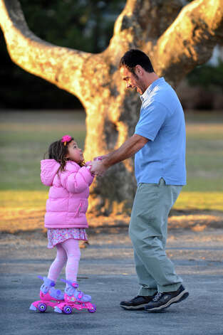 Matthew Michael, of Fairfield, spends some time with his daughter Addison, 5, to help her learn how to roller skate in the parking lot at Jennings Beach in Fairfield, Conn. on Wednesday December 5, 2012. Photo: Christian Abraham / Connecticut Post