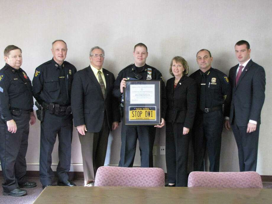Troy Police Officer Ralph Southworth, center, receives a certificate of congratulations from County Executive Kathy Jimino, right. Also pictured, from left, are Troy Police Sgt. David Joslin, Assistant Police Chief George Vanbramer, Mayor Lou Rosamilia, Police Chief John Tedesco and county Special Traffic Operations Director Jim Gordon. (Christopher J. Meyer)